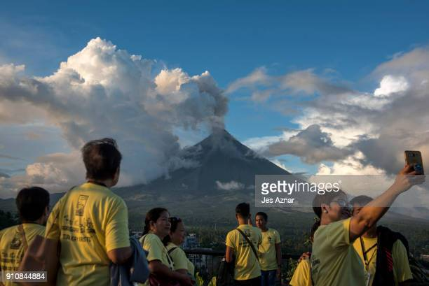 Visitors and residents flock to a viewing area to see Mayon volcano as it erupts on January 26 in Albay Philippines Over 70000 villagers have been...