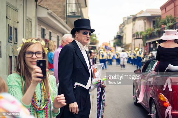 Visitors and residents of the French Quarter enjoying the festivities on St. Philip Street as members of the Chris Owens Easter Parade pass by.