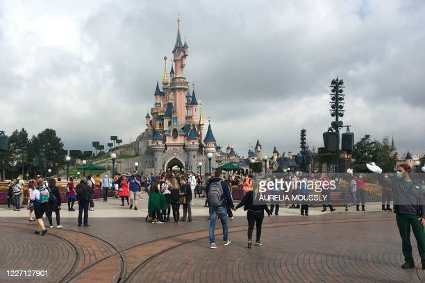 Visitors and staff wearing protective face masks, walk down the Main Street of Disneyland Paris in Marne-la-Vallee, near Paris, on July 15 as...