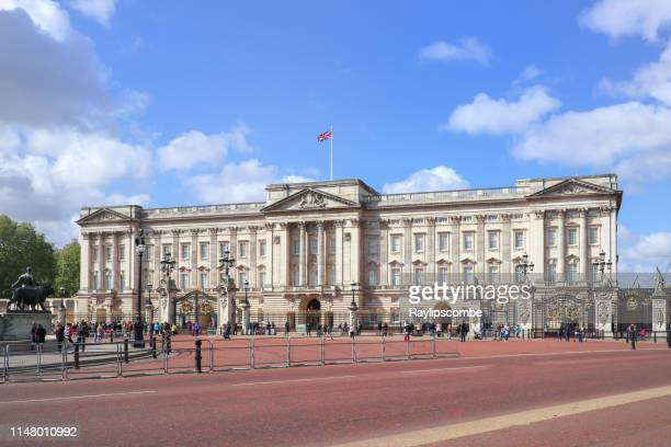 visitors and tourist wandering around the exterior of buckingham palace on a bright sunny day - buckingham palace stock pictures, royalty-free photos & images