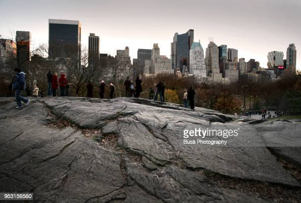 Visitors and tourists atop of Bedrock at Central Park South watching the skyline of Manhattan from Central Park South
