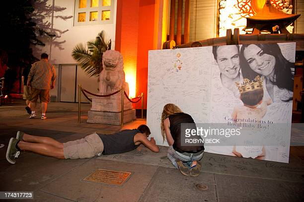 Visitors and tourists sign a giant card congratulating Britain's Prince William and Kate Duchess of Cambridge on the birth of their baby boy outside...