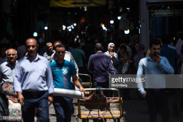 Visitors and traders walk through an arcade inside the Grand Bazaar in Tehran Iran on Monday Aug 6 2018 Irans central bank acting on the eve of US...