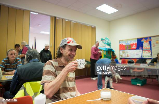Visitors and volunteer drink tea and coffee and have bacon sandwiches at the Salvation Army's weekly dropin morning which coincides with a foodbank...