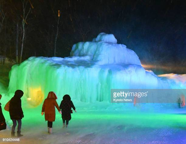 Visitors approach an ice sculpture lit up at the annual ice festival held at the Sounkyo hot spring resort in Kamikawa in the northernmost Japanese...