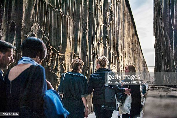 Visitors are pictured walking along the outside of the international pavilion at the Corderie on the first public day of the Venice Biennale May 2015