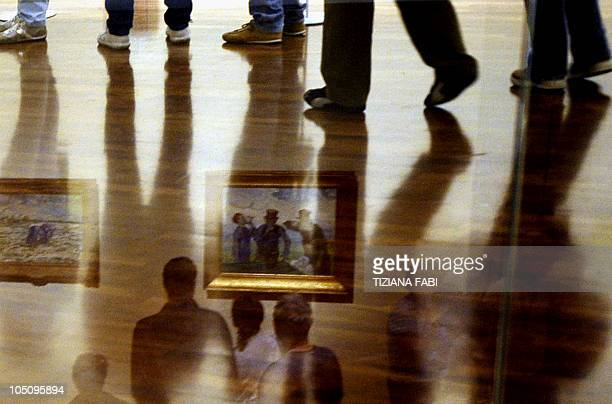 Visitors are reflected as they watch paintings by Dutch post impressionist painter Vincent van Gogh at Vittoriano museum in central Rome on October 9...