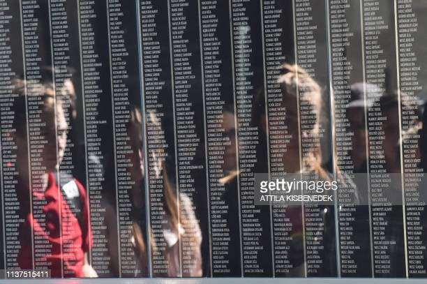 Visitors are reflected by the black marble stone with the names of the Holocaust victims at the Holocaust Memorial Center, first central Europe's...