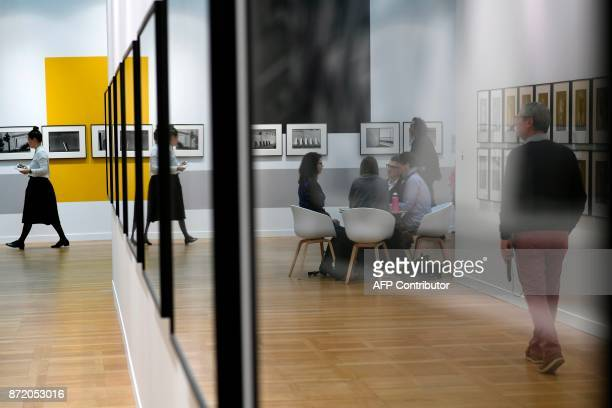 Visitors are reflected in exhibits as they attend 'Paris Photo' at The Grand Palais in Paris on November 9 2017 / AFP PHOTO / Lionel BONAVENTURE