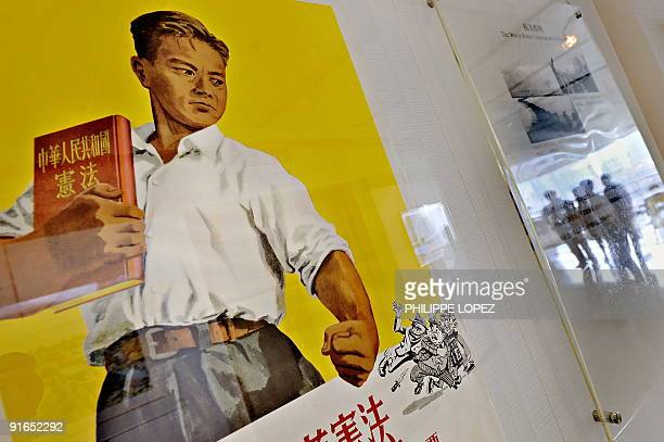 Visitors are reflected next to a propaganda poster during an exhibition in Shanghai on October 8 2009 According to political experts China propaganda...