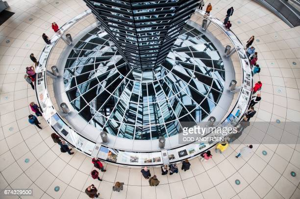 Visitors are seen at the dome of the Bundestag Germany´s lower house of parliament in Berlin on April 28 2017 / AFP PHOTO / Odd ANDERSEN