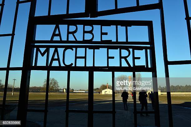 Visitors are seen behind a gate with the inscription 'Arbeit macht frei' on the grounds of the Sachsenhausen memorial of a former Nazi concentration...