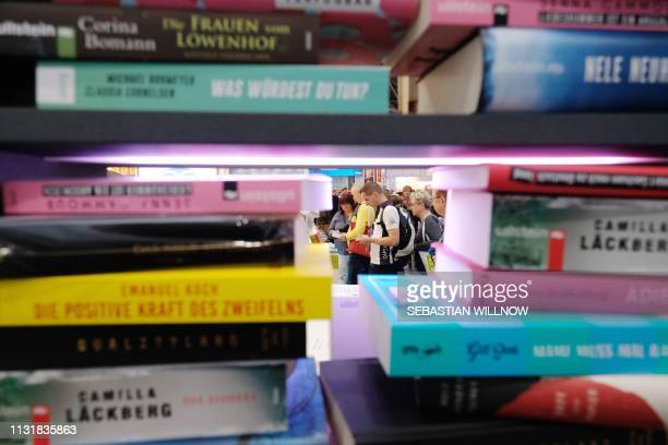 Visitors are seen behind a pile of books on display at the booth of the Random House publishing house at the Leipziger Buchmesse book fair in...
