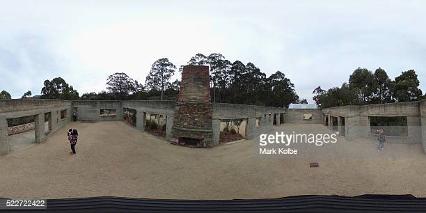 Visitors are seen in the interior of the shell of the Broad Arrow cafe is seen in the Memorial Garden of the Port Arthur Historical Site on April 18...