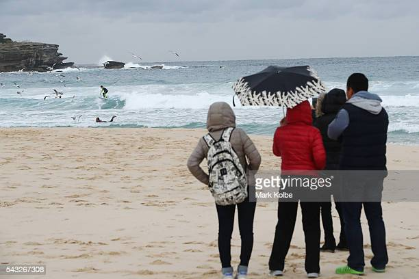 Visitors are seen in winter jackets and huddling under umbrellas as they watch surfers catch waves at Bondi Beach on June 27 2016 in Sydney Australia...