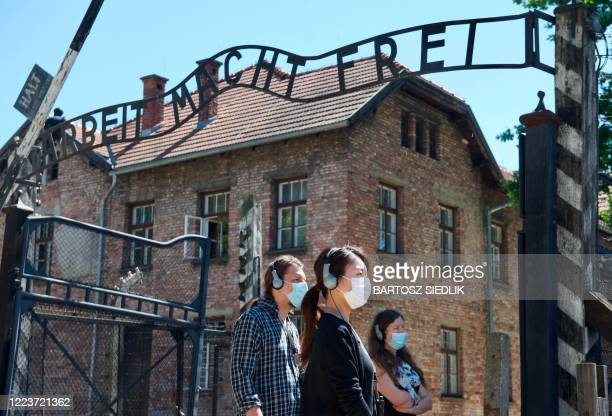 """Visitors are seen near the gate with its inscription """"Work sets you free"""" as the memorial site of the former German Nazi death camp Auschwitz in..."""