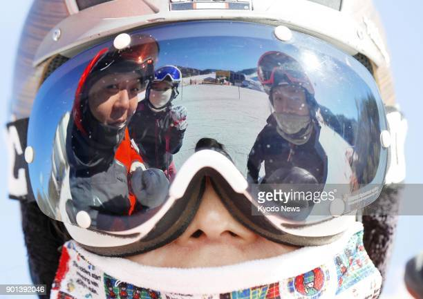 Visitors are seen reflected in a snow goggle at a ski resort in Pyeongchang South Korea on Jan 3 ahead of the Winter Olympics starting in February...