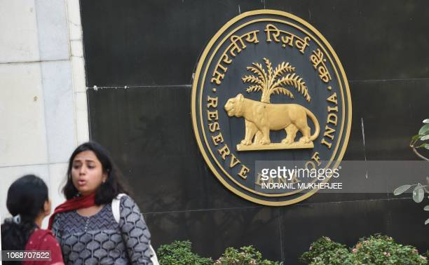Visitors are seen standing next to a logo of the Reserve Bank of India at the bank's head office in Mumbai on December 5 2018 India's central bank...