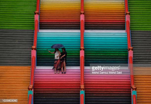 Visitors are seen take their picture on the 272step stairs leading up to the Sri Subramaniar Swamy temple are painted with bright colors on September...