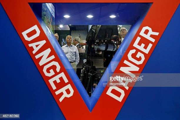 Visitors are seen through a 'Danger' warning sign as they look at an ejector seat used in the Lockheed Martin Corp F35 Lightning II joint strike...