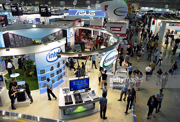 Visitors are seen walking past trade stands, including the Supermicro booth, during the Computex Taipei 2014 expo at the Taipei Nangang Exhibition...