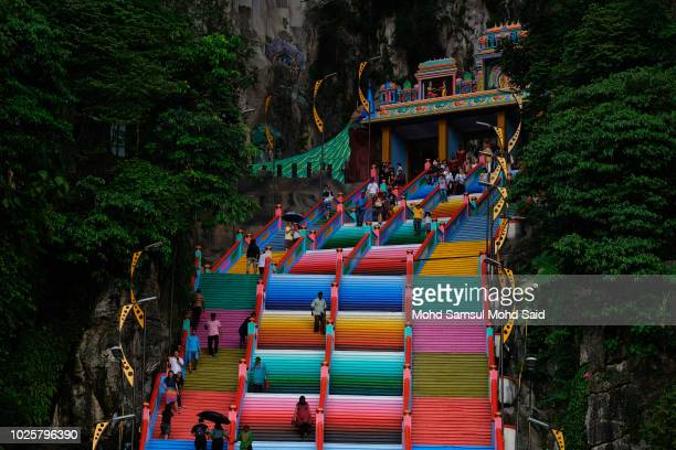 Visitors are seen walks on the 272step stairs leading up to the main entrance of Sri Subramaniar Swamy temple are painted with bright colors on...