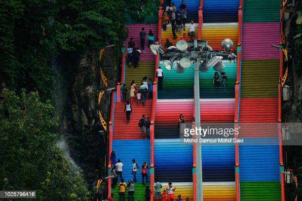 Visitors are seen walks on the 272step stairs leading up to the Sri Subramaniar Swamy temple are painted with bright colors on September 1 2018 in...