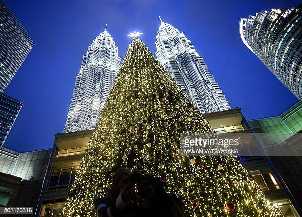 Visitors are silhouetted as they pose for pictures in front of an illuminated Christmas tree near Malaysia's iconic twintowers at a shopping mall in...