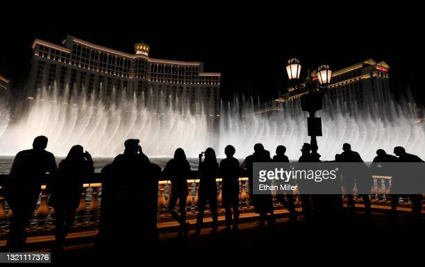 Visitors are silhouetted as they watch The Fountains of Bellagio on May 31, 2021 in Las Vegas, Nevada. Clark County is dropping all pandemic mandates...
