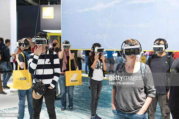 Visitors are trying out the Zeiss VR One Plus video glasses at the 2016 Photokina trade fair on September 24 2016 in Cologne Germany Photokina is the...