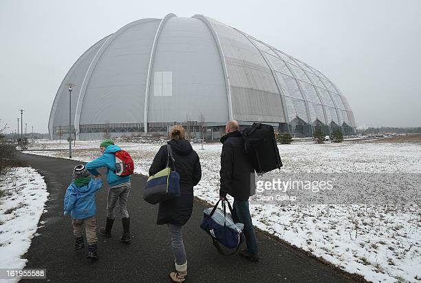 Visitors arrive at the giant hangar that houses the Tropical Islands indoor resort on February 15 2013 in Krausnick Germany Located on the site of a...