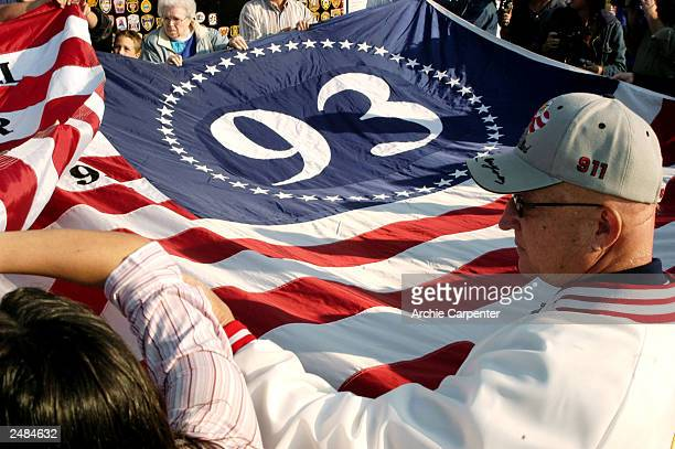 Visitors assist in unfolding a gaint flag at a temporary memorial overlooking the crash site September 11, 2003 in Shanksville, Pennsylvania. The...
