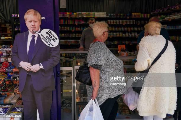 Visitors at a market stall alongside a novelty life-sized cut-out of Boris Johnson, U.K. Prime minister, in Skegness, U.K., on Monday, May 31, 2021....