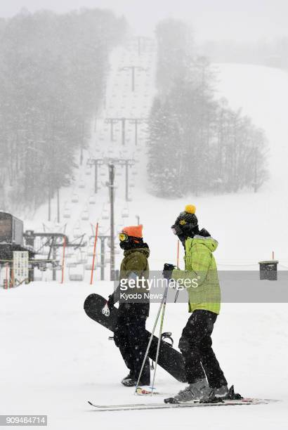 Visitors at a ski resort near Mt MotoShirane in Gunma Prefecture eastern Japan head for the slopes on Jan 24 a day after the active volcano erupted...