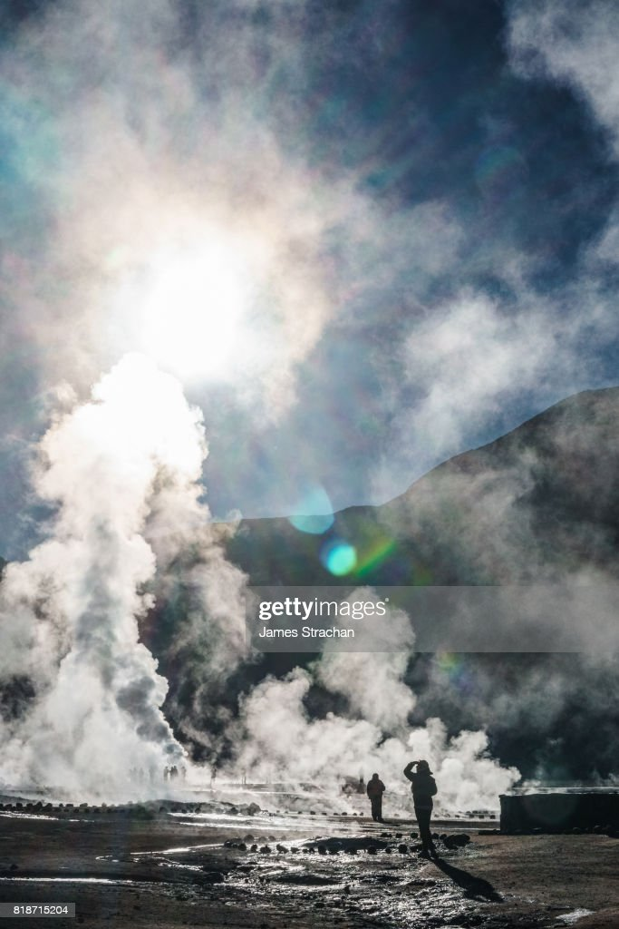 Visitors at dawn watching the sulfur-rich geysers shoot upwards at high altitude (4320m) Geisers de Tatio, near San Pedro de Atacama, Chile : Stock Photo