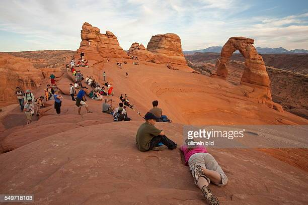 visitors at Delicate Arch in Arches National Park Utah USA