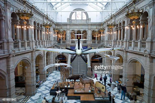 Visitors at Kelvingrove Art Gallery and Museum with suspended Spitfire World War II airplane exhibit on display in the West Court in Glasgow Scotland