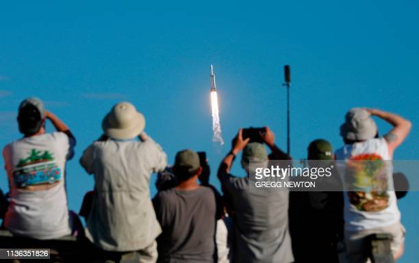 TOPSHOT Visitors at Playalinda Beach look on as a SpaceX Falcon Heavy rocket launches from Pad 39B at the Kennedy Space Center in Florida on April 11...