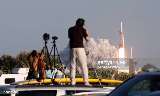 Visitors at Playalinda Beach look on as a SpaceX Falcon Heavy rocket launches from Pad 39B at the Kennedy Space Center in Florida, on April 11, 2019....