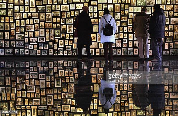 Visitors at the Birkenau Museum on December 10, 2004 view the many faces of the men, women and children at the Auschwitz II - Birkenau which was...