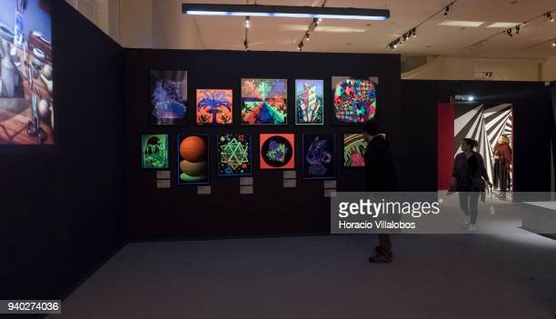 Visitors at the Museu de Arte Popular take in work inspired by Dutch artist Maurits Cornelis Escher on March 30 2018 in Lisbon Portugal This...