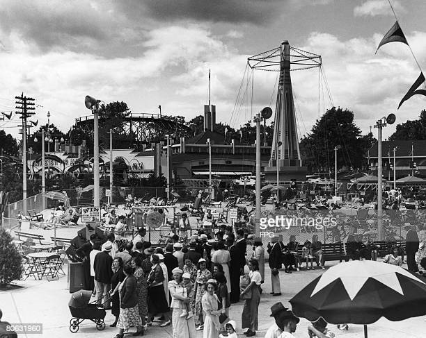 Visitors at the Palisades Amusement Park New Jersey which boasts a sandy 'beach' enclosure and fairground rides circa 1947