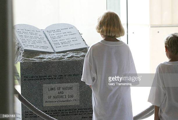 Visitors at the State Judical Building look at a monument of the Ten Commandments in the rotunda August 16 2003 in Montgomery Alabama Alabama Chief...