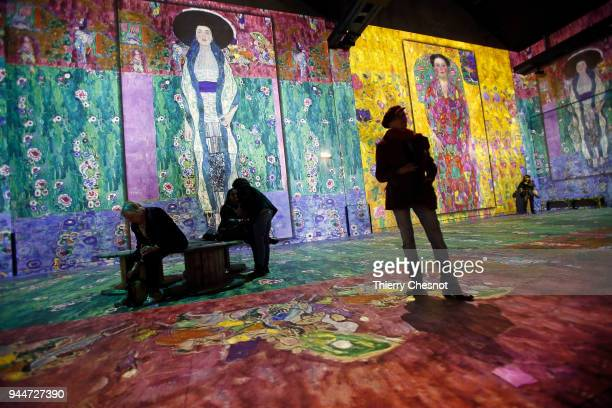 Visitors attend a press preview of the immersive exhibition 'Klimt Hundertwasser Poetic_Ai' that pays tribute to Austrian artist Gustav Klimt at the...