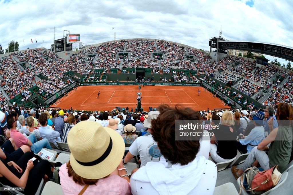 Visitors attend a tennis match during the Roland Garros 2017 French Open on May 30, 2017 in Paris. / AFP PHOTO / Eric FEFERBERG