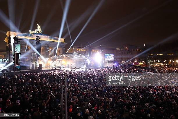 Visitors attend annual New Year's Eve celebrations in front of the Brandenburg Gate on December 31 2016 in Berlin Germany Security was tightened this...