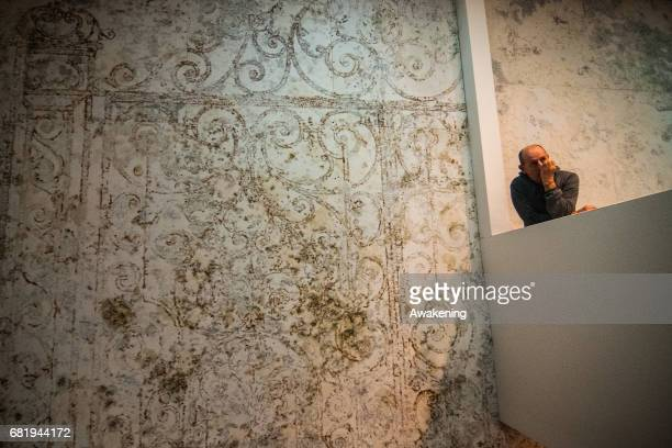 Visitors attend at the opening of the Israel pavilion, presenting the project 'Sun Stand Still' of Gal Weinstein at the 57th Biennale Arte on May 11,...