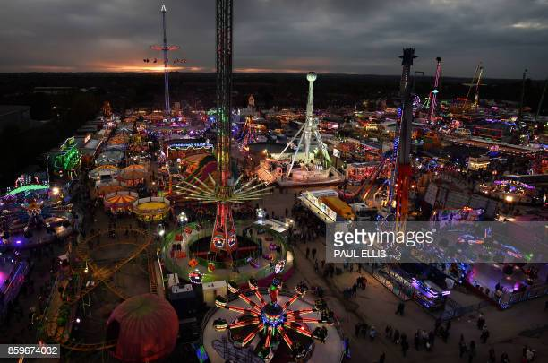 Visitors attend the 'Hull Fair' one of Europe's largest annual travelling fairs in Hull north east England on October 9 2017 Showmen and women have...