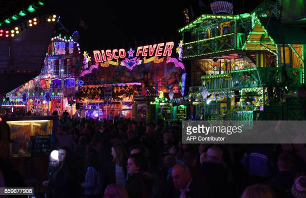 Visitors attend the 'Hull Fair', one of Europe's largest annual travelling fairs, in Hull, north east England on October 9, 2017. Showmen and women...