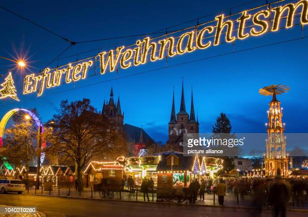 Visitors attend the opening of the Christmas market outside the Severi Church and the Cathedral in Erfurt Germany 22 November 2016 The market is...